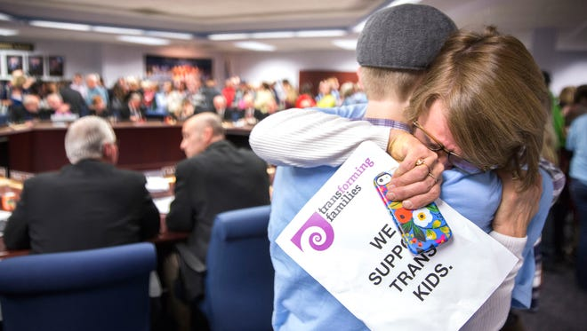 Janae Winegarden of Maple Grove, Minn., hugs her transgender son Seth Thompson, 17, to celebrate after the Minnesota State High School League board voted to pass the Model Gender Identity Participation in MSHSL Activities Policy earlier this month.
