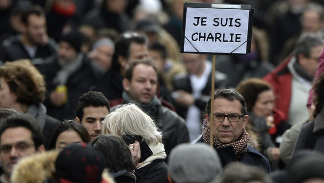 "A man holds a sign in French that reads, ""Je Suis Charlie"" (""I am Charlie"") at the start of a unity rally in Paris on Jan. 11."
