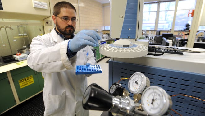 Richard Gualandi removes samples from a diagnostics machine at the A-B Tech biofuels testing lab Tuesday afternoon.