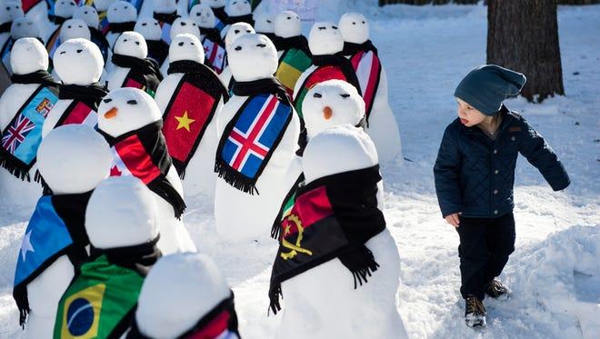 A child walks next to snowmen representing the countries of the world during an exhibition on the sideline of the the World Economic Forum in Davos, Switzerland, Wednesday.
