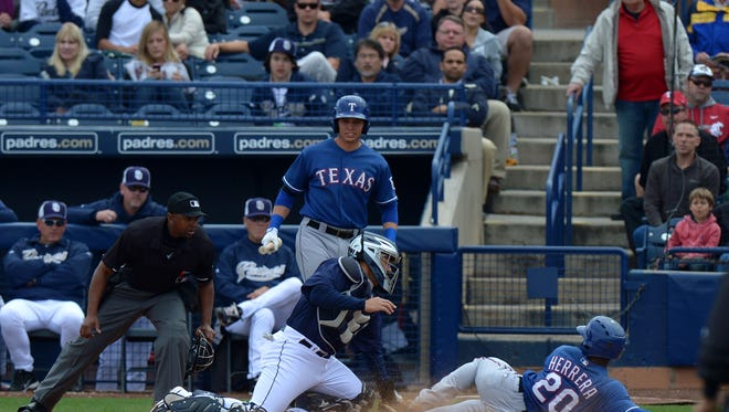 Rangers second baseman Odubel Herrera (20) is tagged out by San Diego Padres catcher Rene Rivera (center) during the sixth inning March 9, 2013 at Peoria Sports Complex. Credit: Jake Roth-USA TODAY Sports