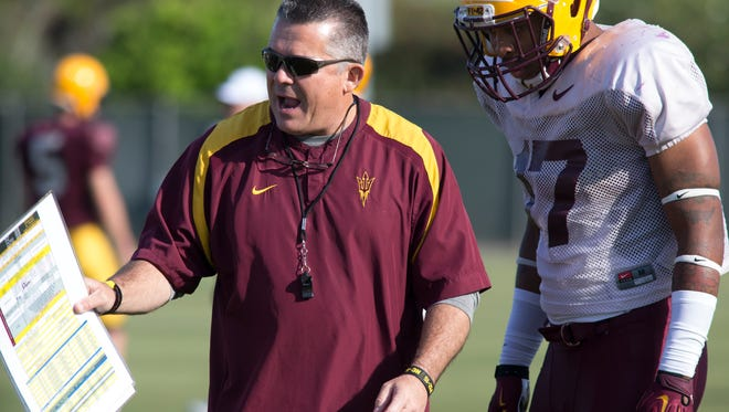 Todd Graham (head coach, left) works with Ismael Murphy-Richardson (17, LB), March 24, 2015, during spring football practice in Tempe.