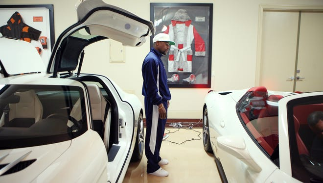 Floyd Mayweather, Jr. stands next to two of his sports cars in one of his garages at his home in Las Vegas