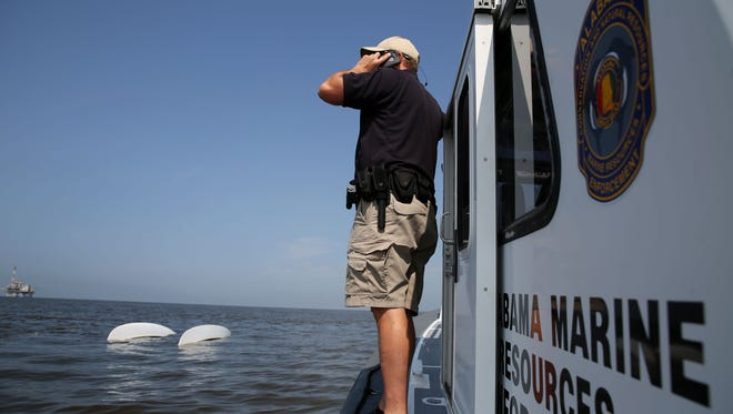 Lt. Jason Downey, of the Alabama Department of Conservation and Natural Resources, calls in a capsized catamaran as search and rescue operations continue  off Dauphin Island, Ala. on Sunday, April 26, 2015. Coast Guard crews continued searching Sunday for five people missing in the water after recovering two bodies following a powerful storm that capsized several sailboats participating in a regatta near Mobile Bay.