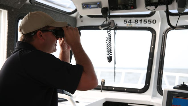 Lt. Jason Downey, of the Alabama Department of Conservation and Natural Resources, looks over the water during search and rescue operations off Dauphin Island.