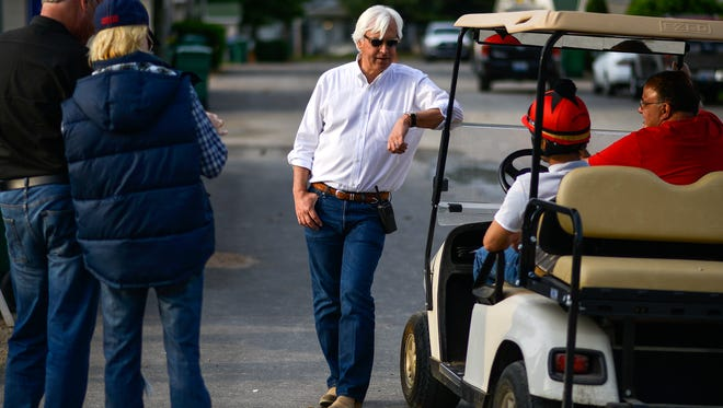Bob Baffert, middle, talks with friends and colleges on the backside of Churchill Downs before exercising American Pharoah on Monday May 11, 2015.