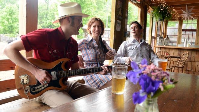 "From left musicians Sam ""Sammy Guns"" Gundlach, Cynthia Galli and Scott Murray converse at the Bywater Riverside Bar."