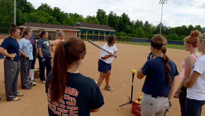 Enka coach Jennifer Kruk demonstrates a drill to her players during practice Monday in Candler.