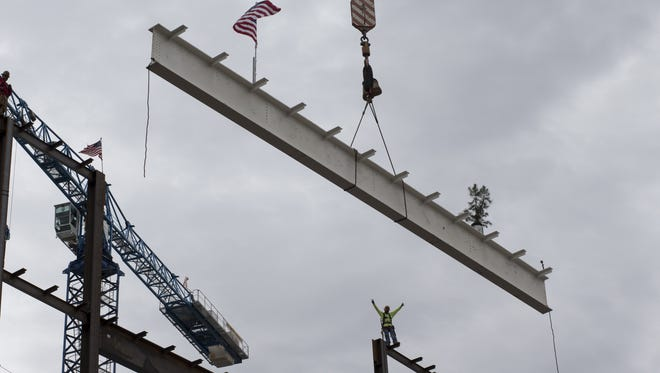 Iron worker Alejandro Covarrubias waits for the final beam to be lifted into place, June 9, 2015, on ASU's Sandra Day O'Connor College of Law, Second and Taylor streets, Phoenix.