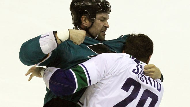 San Jose Sharks John Scott (20) fights with Vancouver Canucks Tom Sestito (29) in a first-period fight.