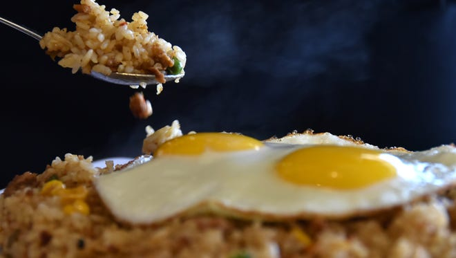 A dark background brings the focus to what matter most: Steam rising from the messy comfort food that is fried rice, and slippery gleaming eggs at The Cafeteria restaurant in Harmon.
