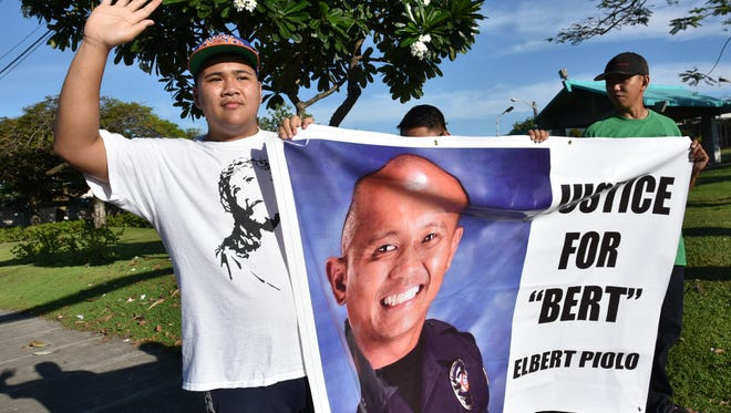 """Jensen Lalu, 15, nephew of the late Guam Police Department Officer Elbert Piolo, joins others in a demonstration at the ITC intersection Thursday morning. Piolo's cousin Gabby Macaraeg, right, said he was at """"a loss of words"""" after his death. """"How can this good man deserve this kind of situation,"""" he said."""