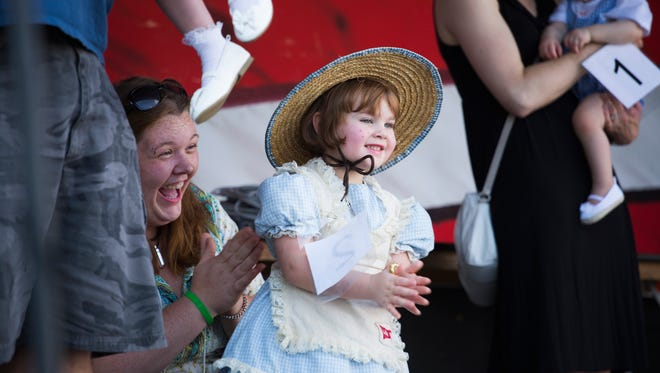 Summer Meadows, 4, of Waynesboro, steps forward after being announced the winner of the Little Debbie look-alike contest while her mom, Victoria Kiser, cheers her on at the 12th Annual Sweet Dreams Festival in Stuarts Draft on Saturday, July 25, 2015.
