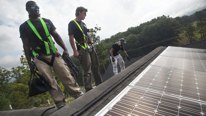 Workers with Sigora Solar stands on the roof of a home being constructed by Habitat for Humanity after installing a series of solar panels in Waynesboro on Thursday, Sept. 4, 2014.