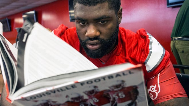 UofL offensive lineman Kelby Johnson checks out the 2015 Louisville Football Guide during Media Day at Papa John's Stadium on Saturday morning. 8/8/15