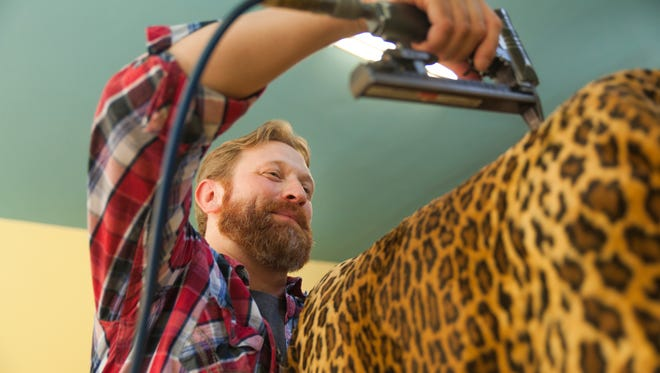 Travis Norton, who own's Norton Upholstery on West Beverley Street in Staunton, restores a customer's leopard print chair in his shop on Tuesday, Sept. 15, 2015.