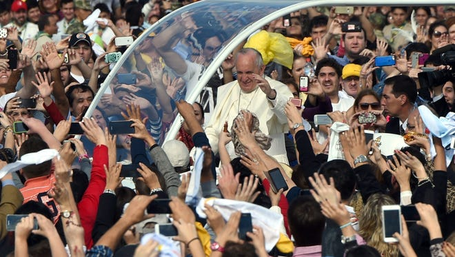Pope Francis rolls through Asuncion, Paraguay, in July 2015 in an open-sided car, which he prefers.