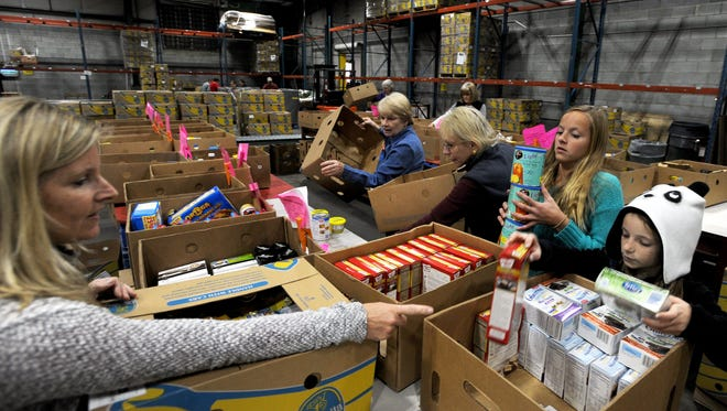 From left, Kris Hemmel, Kathy Bronson, Pat Newstedt, 13-year-old Keely Hemmel and 10-year-old Riley Hemmel package boxes of food for needy families Tuesday afternoon at MANNA Food Bank on Swannanoa Road. The nonprofit is joining forces with local schools to call for reform of the Healthy Hunger-Free Kids Act which expires this month.