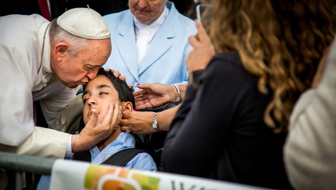 In this photo provided by World Meeting of Families, Pope Francis kisses and blesses Michael Keating, 10, of Elverson, Pa., after arriving in Philadelphia and exiting his car when he saw the boy, on Sept. 26, 2015, at Philadelphia International Airport.