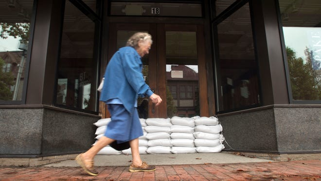 A woman walks past sand bags protecting a business at 18 Sweeten Creek Road Friday afternoon a head of projected flooding in the Biltmore Village area.