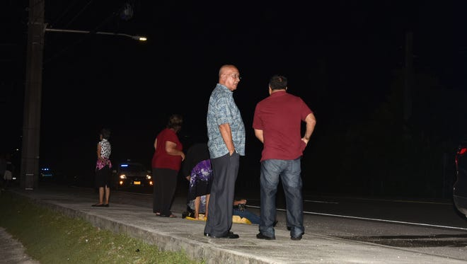 The pedestrian's family, including brother Danny Santos, second from right, watch police investigate a fatal accident in Asan on Saturday, Oct. 3.