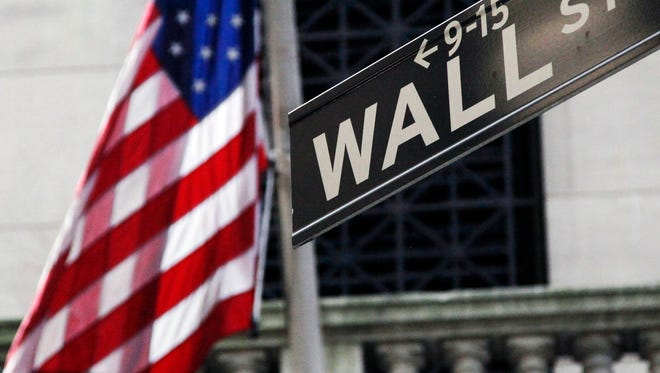 This July 15, 2013 file photo shows the American flag and Wall Street street sign outside the New York Stock Exchange, in New York.  (AP Photo/Mark Lennihan, File)