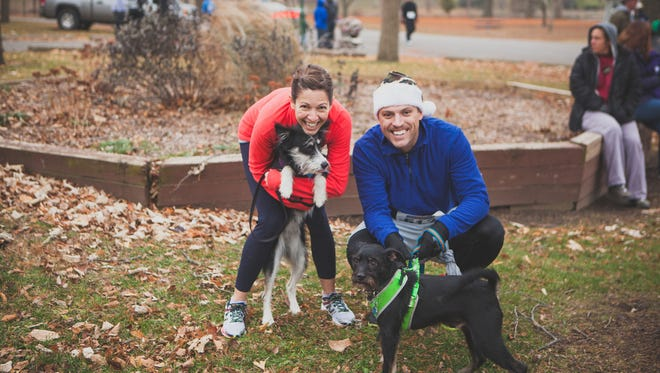 Luke Feeney, right, and his wife, Stacy Brooks, poses with their dogs after the 2014 Turkey Trot in Yoctangee Park.