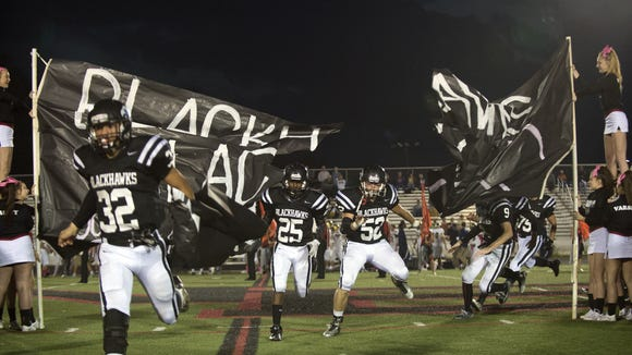 North Buncombe football players run through their banner Friday in Weaverville