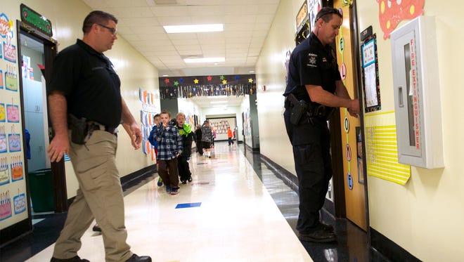 Henderson County Sheriff deputies Lt. Neil McDonald, left, and Steve Geyer unlock classrooms following a training lockdown of the Marlow Elementary School Thursday morning.
