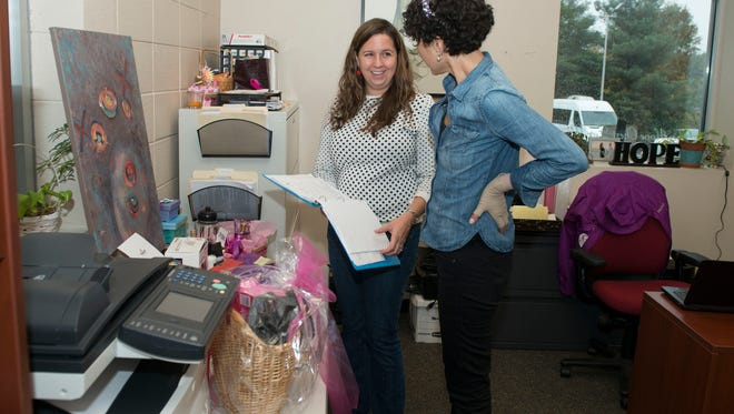 Hope Chest for Women Executive Director Sara Shuster Laws and Asheville Citizen-Times writer Karen Chavez sort silent auction items for a fashion show benefiting Hope Chest for Women at their office located behind the Foster Seventh Day Adventist Church off Hendersonville Road.