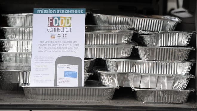 Donated food sits in an Asheville Taxi behind Chestnut Monday Jan. 26, 2015. The food was leftover from the Winter Warmer Festival.