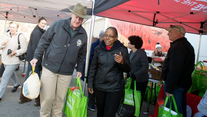Asheville resident Delores Scruggs get help with a turkey and a bag of groceries from U.S. Representative Mark Meadows, R-NC, during a holiday grocery give-a-way provided by Eblen Charities and Ingles Wednesday morning at the Eblen Charities offices in the Westgate shopping center.
