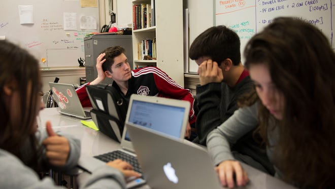 Asheville High School students from left, Rachel Krammer, Evan Rhatigan, Ascher Walker Wilson and Miksa Kavcheski huddle together on a project in Will Smith's english class Tuesday.