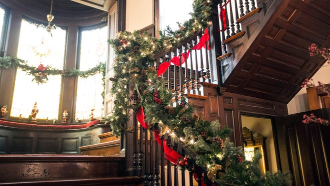 The stairwell banister in the Mengel Mansion on South Third Street receives a holiday makeover. 12/3/15
