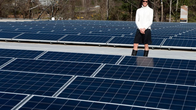 Highland Brewing president Leah Ashburn stands in the middle of a 1,000-panel solar array on the roof of the brewery.