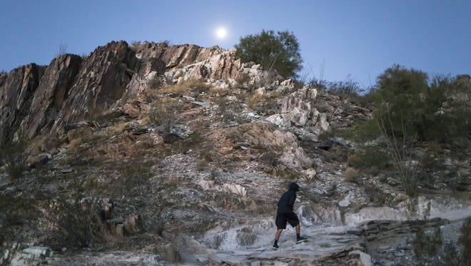 Ramon Rodriguez braves the cold as he makes his way up the trail at Piestewa Peak on Dec. 28, 2015.