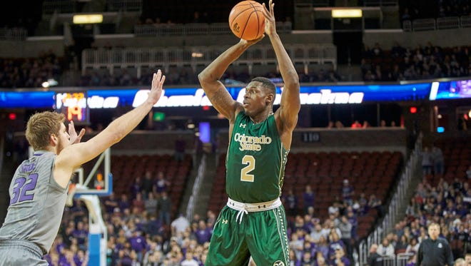 CSU basketball player Emmanuel Omogbo makes a pass over Kansas State defender Dean Wade during a Dec. 19 game in Wichita, Kansas. Omogbo's parents, along with a niece and nephew, were killed in a fire at the family's home early Tuesday in suburban Washington, D.C.