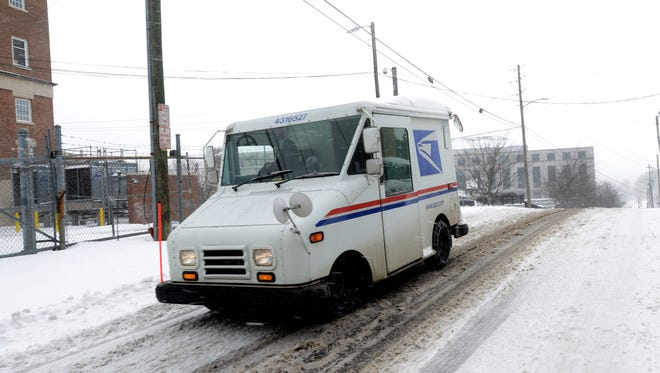 A United States Postal Service vehicles makes its way around the snowy streets of downtown to deliver mail on Saturday, Jan. 23, 2016.