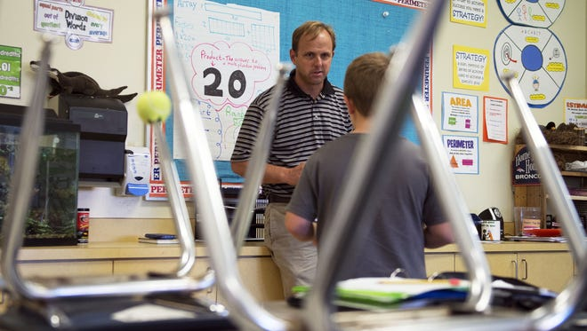 Fourth-grade teacher Geoff Kinsey works with a student  after school to complete math homework last year at Marlow Elementary in Mills River. School superintendents who spoke to a state House committee last week said they have had trouble filling vacancies for elementary school teachers recently, something that previously was never a problem.