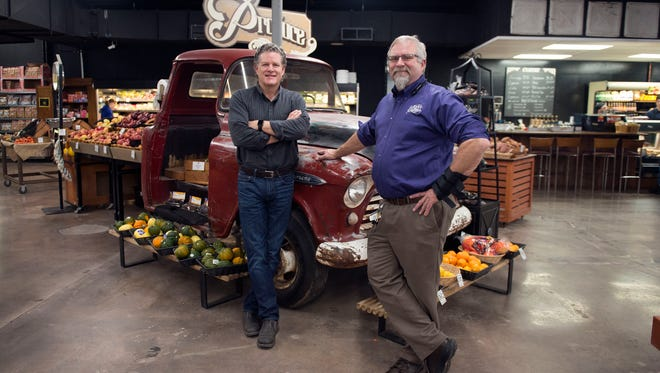 Developer Charlie Ball, left, stands with Hopey & Co. grocer Troy Hopey next to a old Chevy pick-up turned, grocery display at Hopey & Co., located at 45 South French Broad Avenue in downtown Asheville.