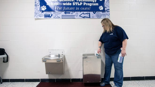 Two of the six water fountains at Brandeis Elementary are sanitized and flushed by custodian Tammy Beisler on Thursday morning before the students arrive. 3/10/16