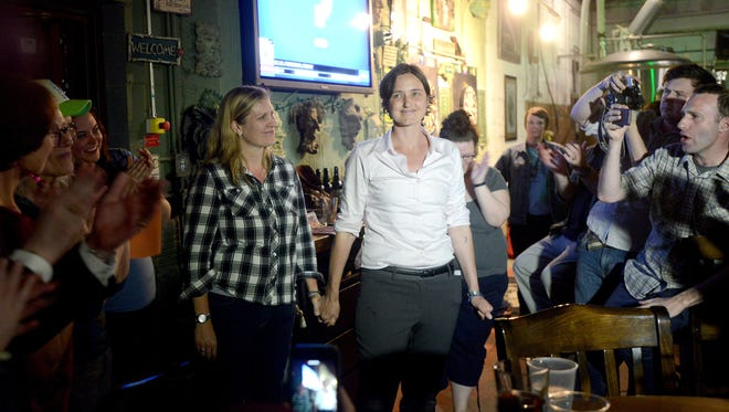 Standing with her wife, Meghann Burke, Jasmine Beach-Ferrara is applauded by her supporters as she gives an acceptance speech after winning the Democratic primary election for Buncombe County Board of Commissioners for District 1 at Green Man Brewery on March 15, 2016. Beach-Ferrara announced that she would seek re-election in 2020.