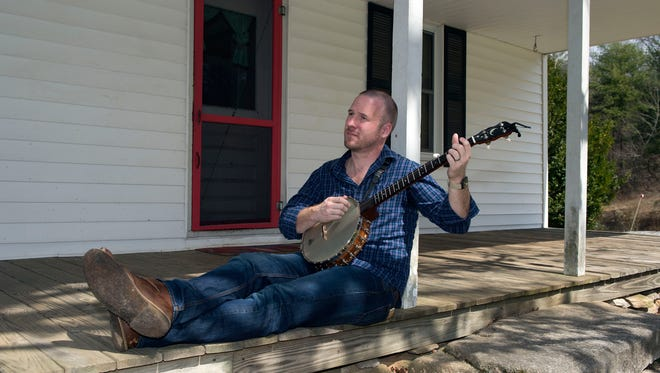 """Local author Jeremy B. Jones noodles on his banjo at his family land in Edneyville. Jones has written """"Bearwallow"""" which has been selected for the AC-T Book Circle selection for March."""