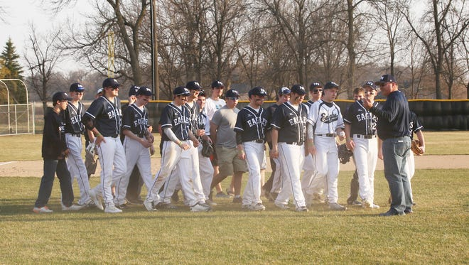 The Eden Valley-Watkins prep baseball team joins Jake Foehrenbacher's father, Don, on the field before the start of the game Thursday in Eden Valley.
