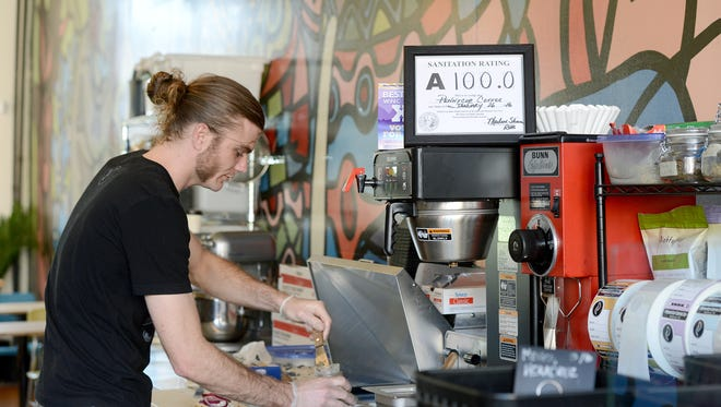 Matthew Burd, owner of PennyCup Coffee at the YMI, makes an order for a customer at the restaurant on Tuesday, April 26, 2016. The coffee shop received a 100 sanitation rating at their inspection in January.