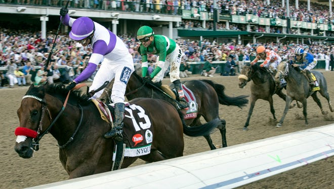 Jockey Mario Gutierrez raises a fist as he crosses the finish line atop winner Nyquist during the 142nd running of the Kentucky Derby on Saturday afternoon. 5/7/16