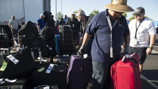 Baggage in the special events parking lot is loaded into a truck, May 12, 2016, at Phoenix Sky Harbor International Airport.
