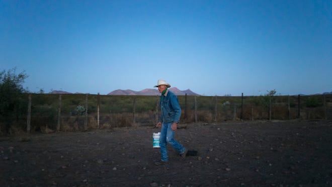 A rancher walks across the open land in Douglas, Arizona.