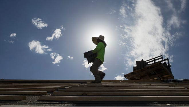 Jorge Gonzalez works on a home under construction on July 27, 2016, at the Grove in Phoenix.