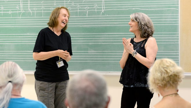 Marie Vanderbeck, of Pittsboro, left, laughs as she gets singing advice from country and bluegrass singer Kathy Mattea in her workshop at Warren Wilson College during the Swannanoa Gathering on Wednesday, July 27, 2016.